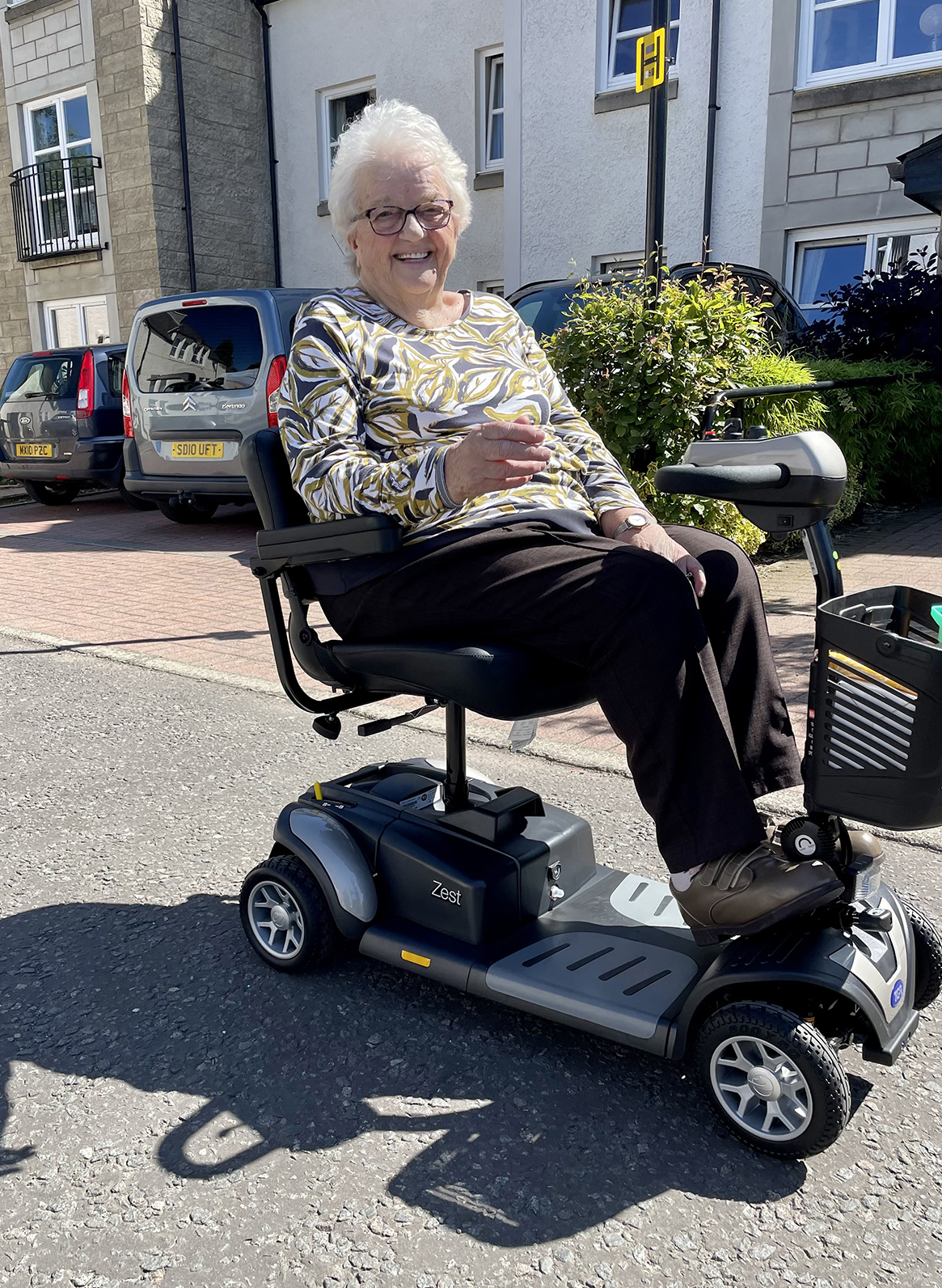 Margaret Simpson from Peebles proudly driving her new Zest mobility scooter from TGA.
